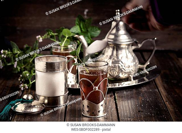 Pouring sugar into traditional North African tea with fresh mint leaves