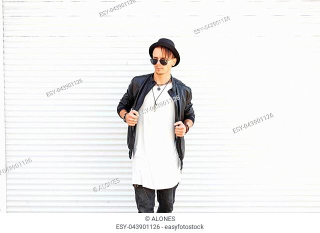 Stylish model man in a trendy hat with sunglasses in a trendy black jacket and a white t-shirt near metal doors