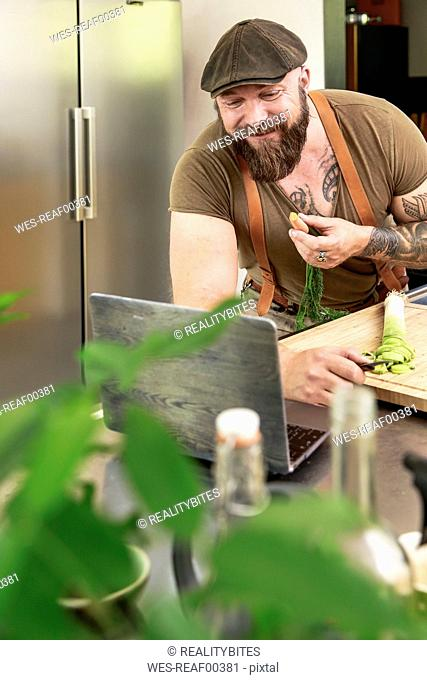 Mature man trying out vegetarian online-recipes