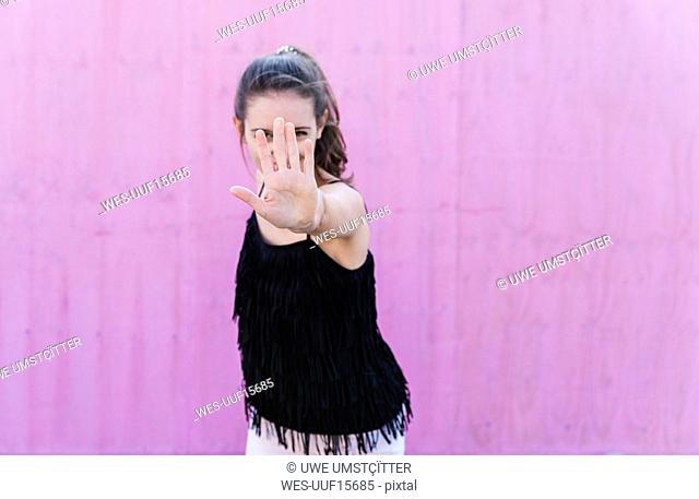 Young woman standing in front of pink wall raising her hand
