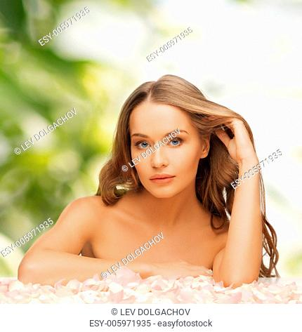 health and beauty concept - beautiful woman with rose petals and long hair