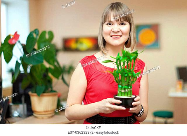 Young woman with lucky bamboo plant at her home