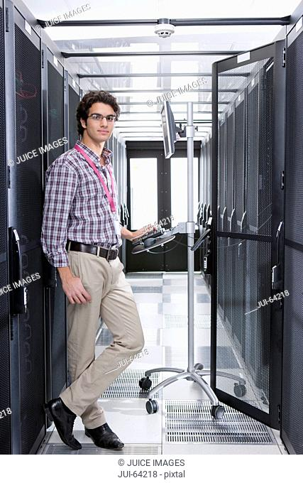 Technician, looking at camera, working on computer in aisle of server storage cabinets