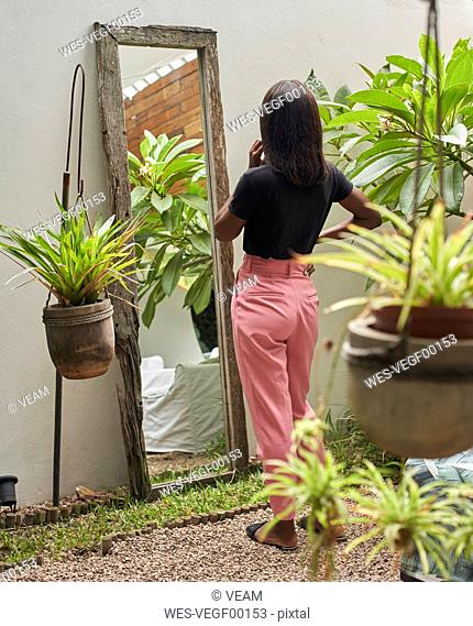 Back view of woman standing in a courtyard looking at mirror