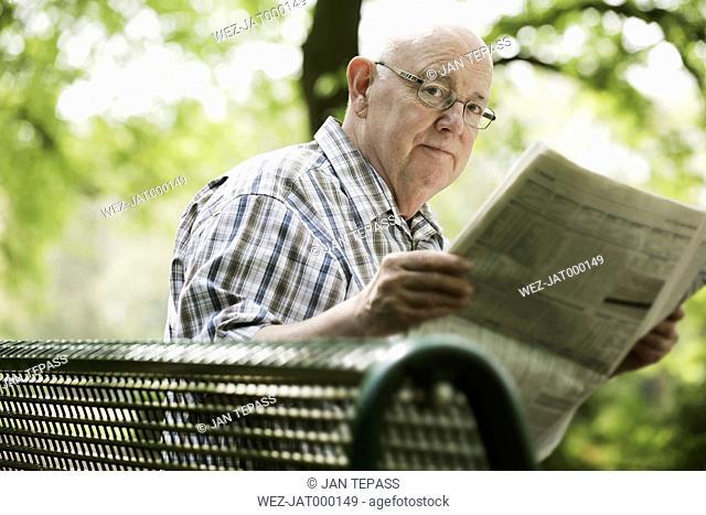 Germany, North Rhine Westphalia, Cologne, Portrait of senior man reading newspaper on bench in park