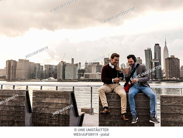 USA, New York City, two young men with headphones and cell phone sitting at East River