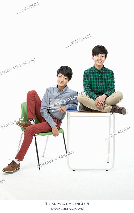Two smiling school boys in casual clothes posing on a chair and a desk