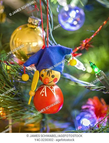 Small Christmas oraments hanging on a Christmas tree