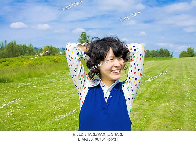 Happy Asian woman standing in park