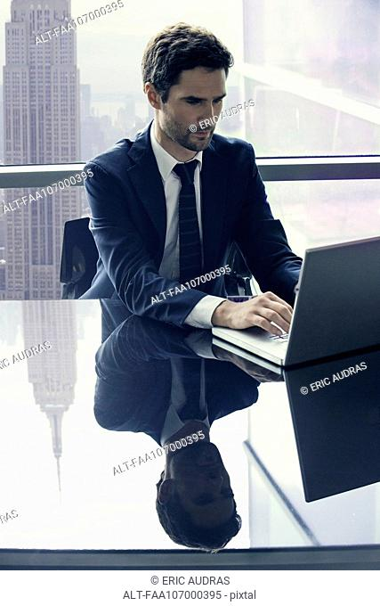 Businessman using laptop computer alone at conference table