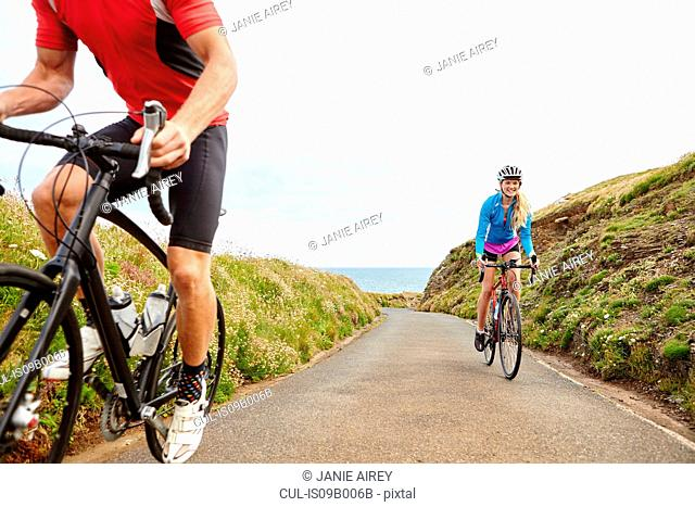 Cyclists riding on road overlooking ocean