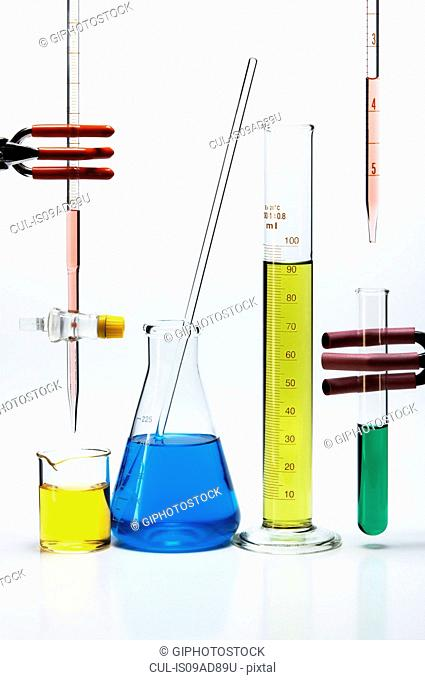Chemical lab glassware: burette over beaker, Erlenmeyer flask with stirring rod, graduated cylinder, pipette over test tube