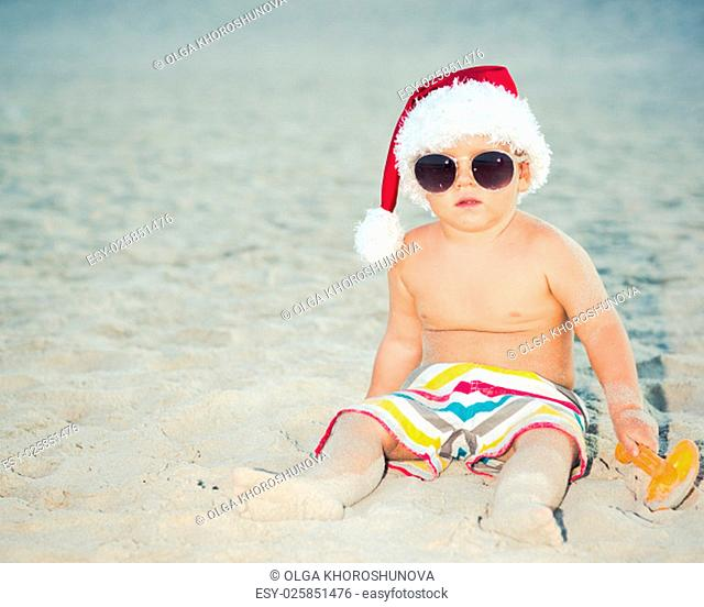 Cute baby wearing Santa hat on the beach