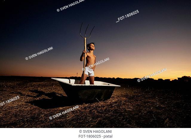 Portrait confident boy in underwear holding pitchfork in bathtub in rural field