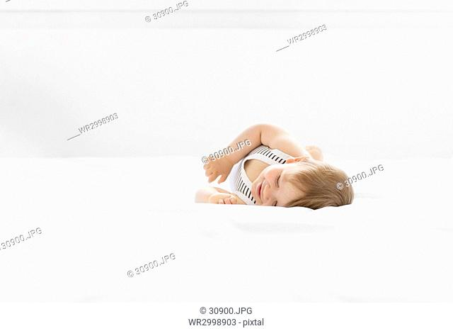 Baby boy wearing striped onesie lying on bed with white duvet