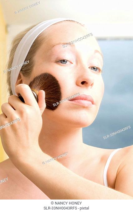 Woman brushing powder onto her face