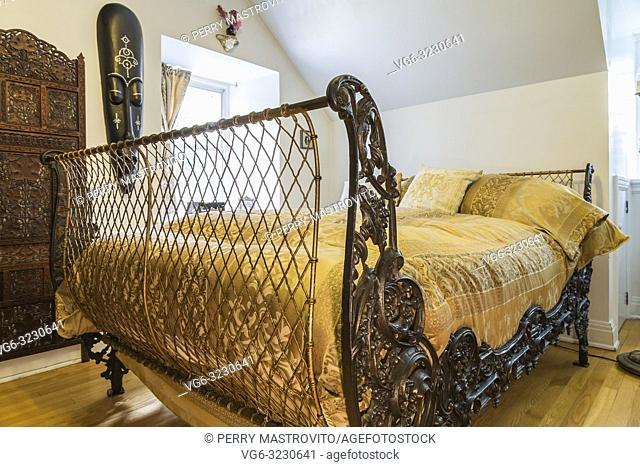 3/4 bed with 200 year old French metal grill style headboard and footboard in upstairs guest bedroom inside an old 1839 Canadiana fieldstone style house