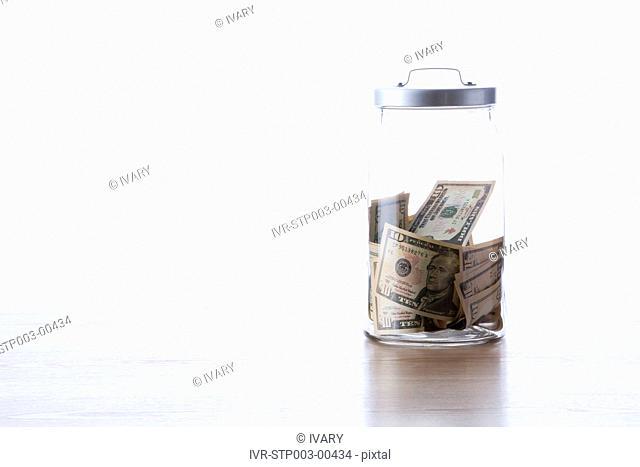 American dollar bills inside of glass jar
