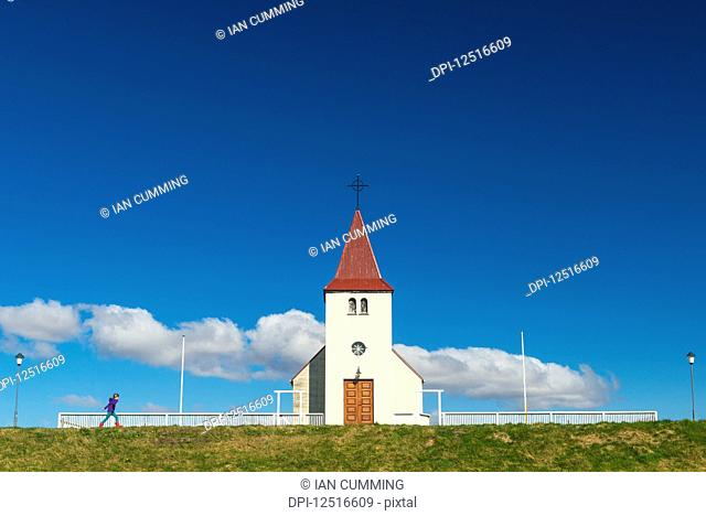 Girl walking past small church; Langaholt, Iceland