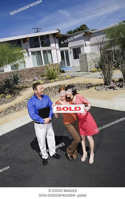 Lesbian couple holding sold sign in front of new house