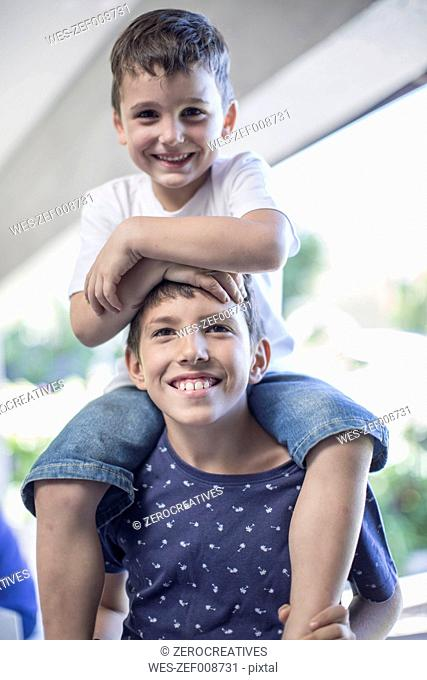Little boy sitting on his brother's shoulders