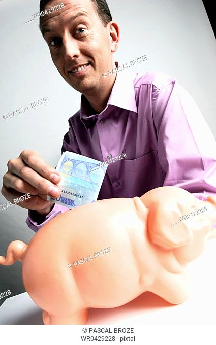 Portrait of a mid adult man inserting money into a piggy bank