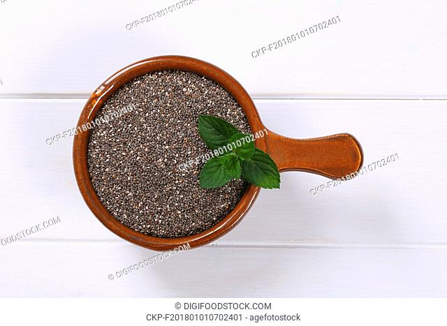 saucepan of chia seeds on white wooden background