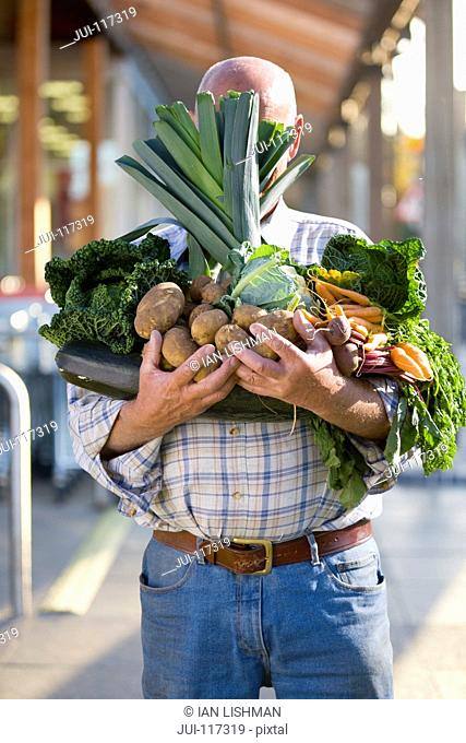 Man Hidden Behind Armful Of Produce Outside Supermarket