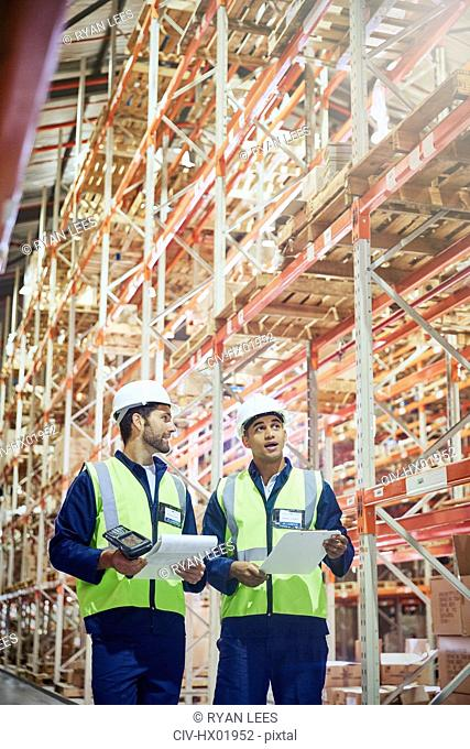 Workers with clipboards and scanner talking in aisle of distribution warehouse
