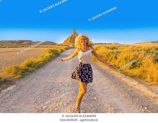 Woman dancing on a path in deserted landscape in the Bardenas desert, Aragon, Spain