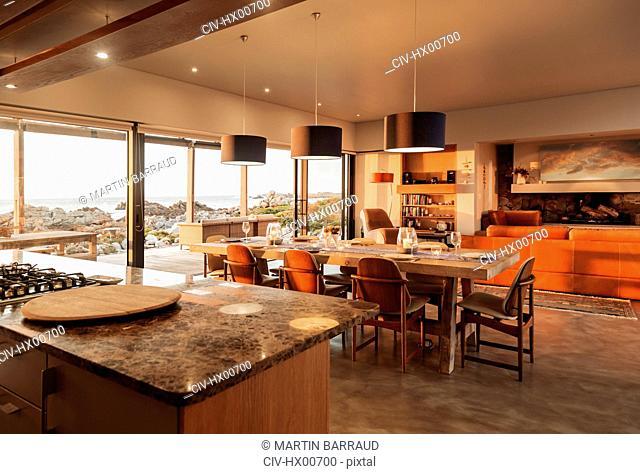 Sunny home showcase interior overlooking ocean
