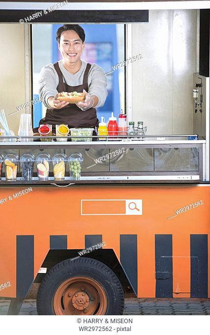 Young smiling vendor selling hotdog at truck