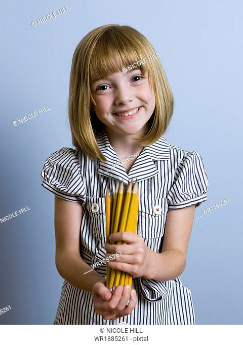 girl holding a bunch of pencils