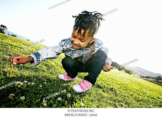 Black girl picking flowers in field