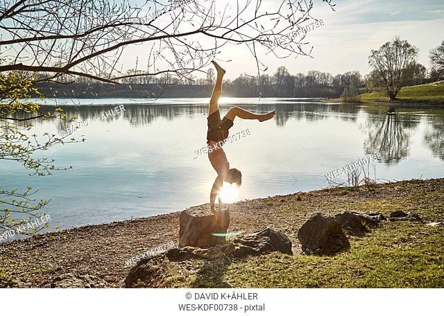 Germany, Bavaria, Feldkirchen, man doing a handstand at lakeshore
