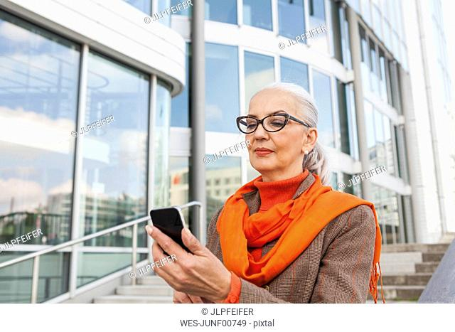 Portrait of fashionable mature woman looking at cell phone