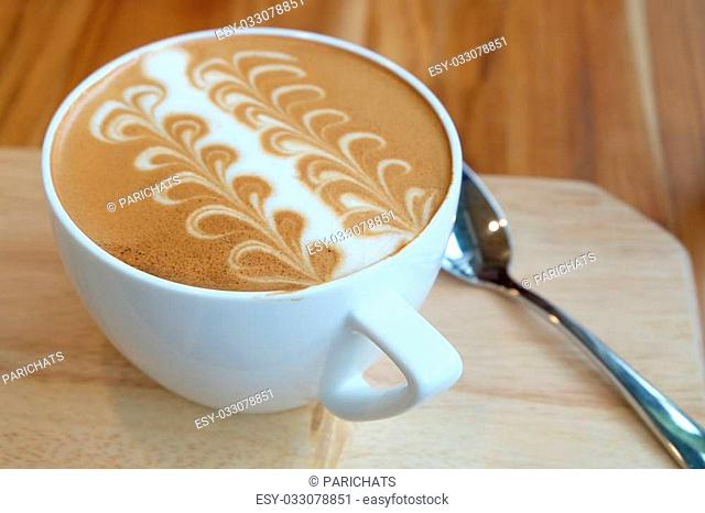 A white cup of Caffe Latte Art on wood tray