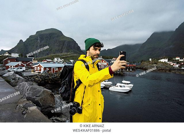 Norway, Lofoten, young man in a fishing village at the coast taking a selfie
