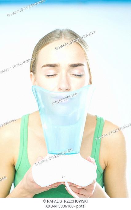 young woman using inhaler