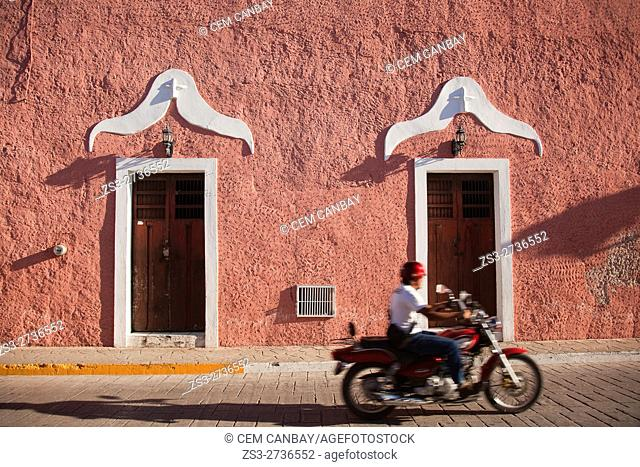 Motorcyclist in front of the colonial buildings in Calzada De Los Frailes at the historic center of the town, Valladolid, Yucatan Province, Mexico