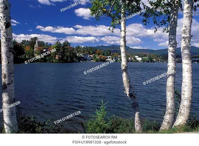 Lake Placid, New York, The Adirondacks, NY, Scenic view of the resort town of Lake Placid thru birch tree along Mirror Lake in the autumn