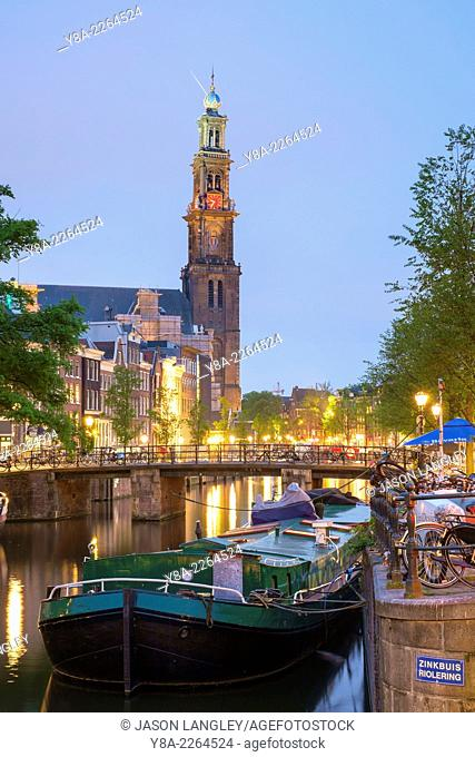 Prinsengracht canal and boat at dusk with tower of Westerkerk in distance, Amsterdam, North Holland, Netherlands