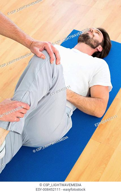 Physical therapist examining man's leg