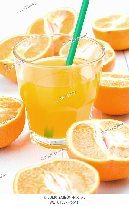 glass of juice and oranges cut in half on white wooden board