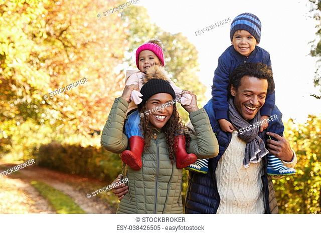 Autumn Walk With Parents Carrying Children On Shoulders