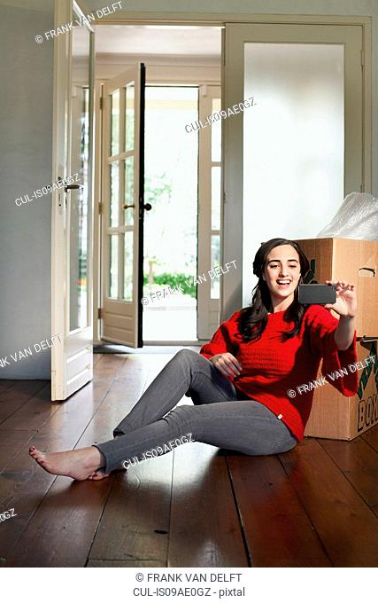 Young woman taking self portrait in new house