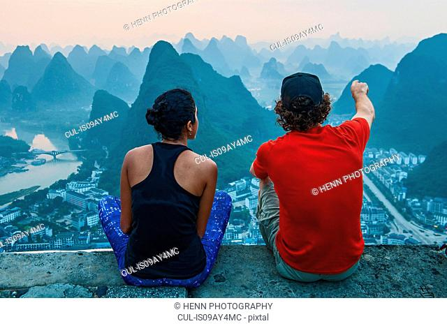 Couple enjoying morning view over Karst Mountains of Guangxi and Yangshuo, China