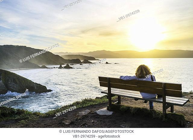 Solo woman sitting at a bench at sunset by the Loiba cliffs (Acantilados de Loiba) Coruña province, Galicia, Spain, Europe