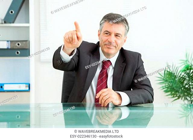 Businessman sitting at his desk pointing at something