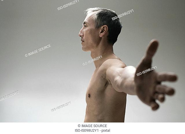 Mature man with arms outstretched